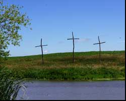 image of three crosses next to pond