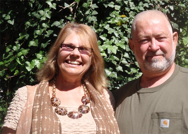 Image of smiling woman named Margie standing next to her husband named Bob with green foliage in the background