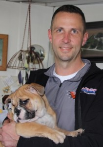 Image of Man standing holding his new English Bulldog Puppy