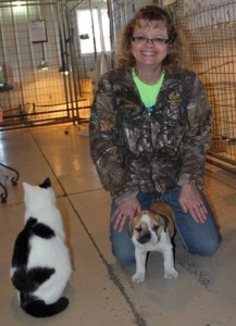 Image of Woman kneeling on floor with new English Bulldog Puppy between her legs purchased from Jimtown Kennels