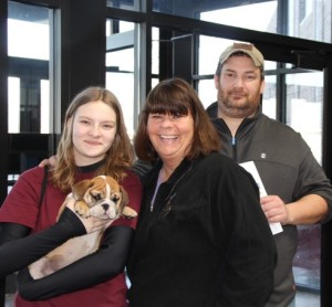 Image of two standing women with man in background. Woman on left is holding her new English Bulldog Puppy from Jimtown Kennels