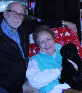 Women setting in chair holding black labradoodle with man kneeling beside her.