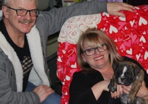 image of couple with wife holding brindle male English Bulldog puppy