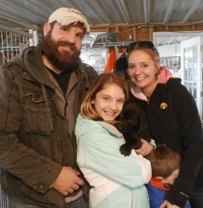 Image of Couple and young girl with their black lab puppy from Jimtown Kennels