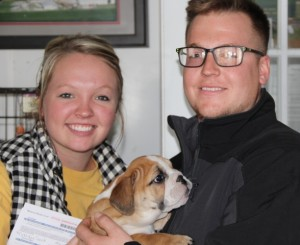 Image of standing woman next to standing man holding new English Bulldog Puppy purchased from Jimtown Kennels