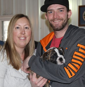 Image of smiling woman and smiling man who is holding his new English Bulldog Puppy from Jimtown Kennels