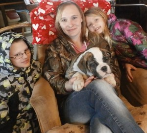 Image of Woman named Tara sitting in a chair holding an English Bulldog from Jimtown kennels with a child on each side of her