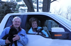 Image of woman setting in truck on passenger side holding dog with man standing beside passenger door holding black female labradoodle.